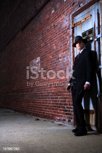 A 1940s style gangster or detective on the lookout in a dark alley.