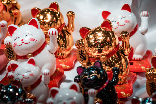 """Fortune cats. Oriental souvenirs, mass produced for international export and trade. Close up shot, artificial lighting. Concept image for economic war between China and America. Mass production into the European market. Traditional icons for sale. Export and trade of """"made in China"""" objects. Economy issues deregulation stock pictures, royalty-free photos & images"""