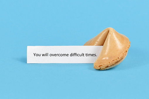 Whole unopened fortune cookie with motivational text on white paper saying 'You will overcome difficult times' on blue background
