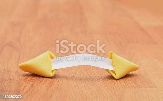 istock Fortune cookies broken with piece of paper without future prediction on the wooden table 1329802070