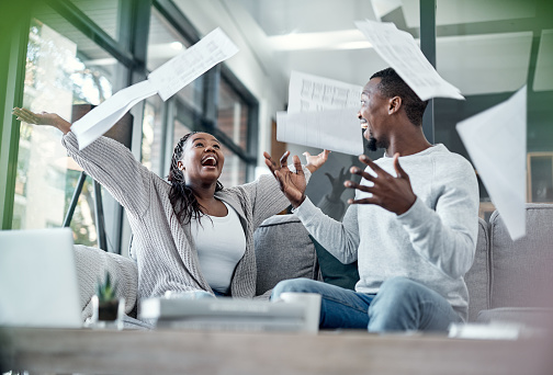 Shot of a young couple celebrating while going through paperwork at home