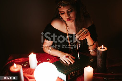 Young female fortune teller and book of spells.