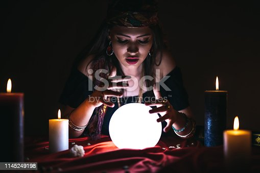 Young female fortune teller is looking into glowing crystal sphere