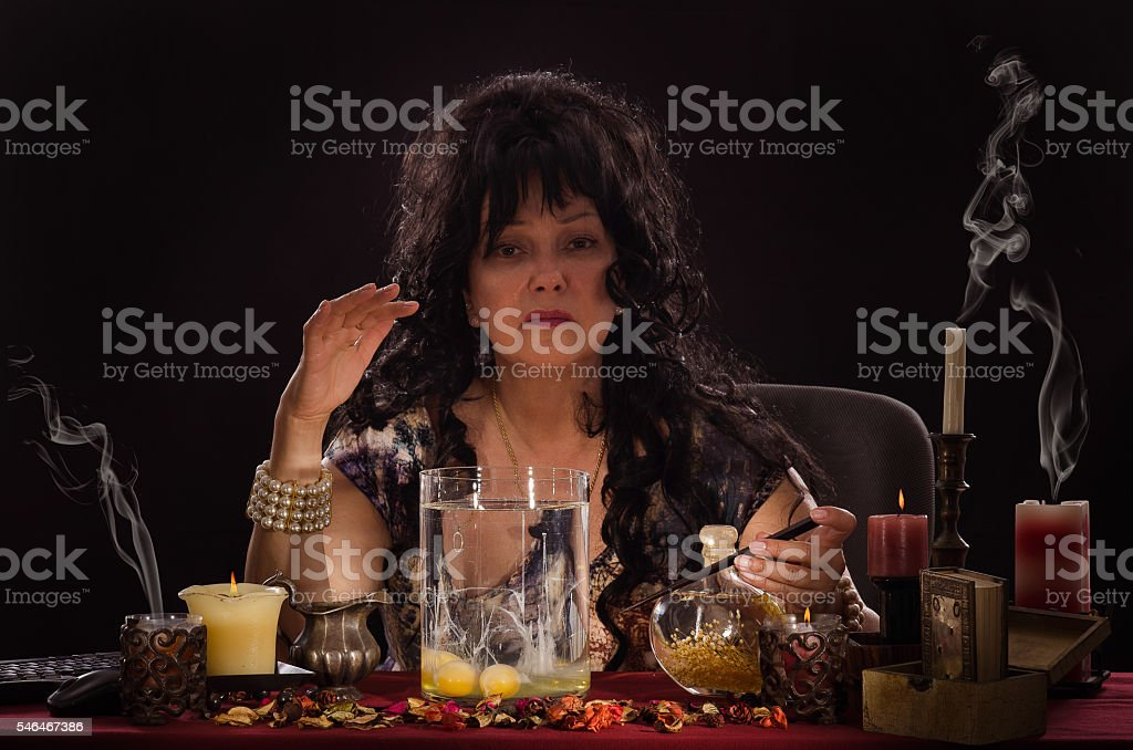 Fortune teller doing egg divination at the desk stock photo