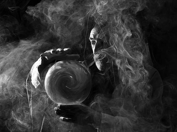 Fortune teller in fantastical costume holding crystal ball Fortune teller in fantastical costume holding crystal ball, smoky atmosphere romani people stock pictures, royalty-free photos & images