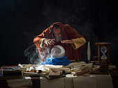 Fortune teller in fantastical costume using crystal ball