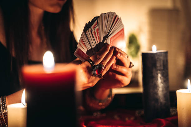 Fortune teller reading tarot Young female fortune teller is looking into tarot cards romani people stock pictures, royalty-free photos & images