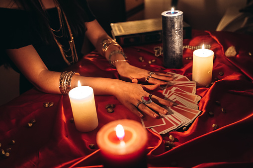 Young female fortune teller reading tarot.