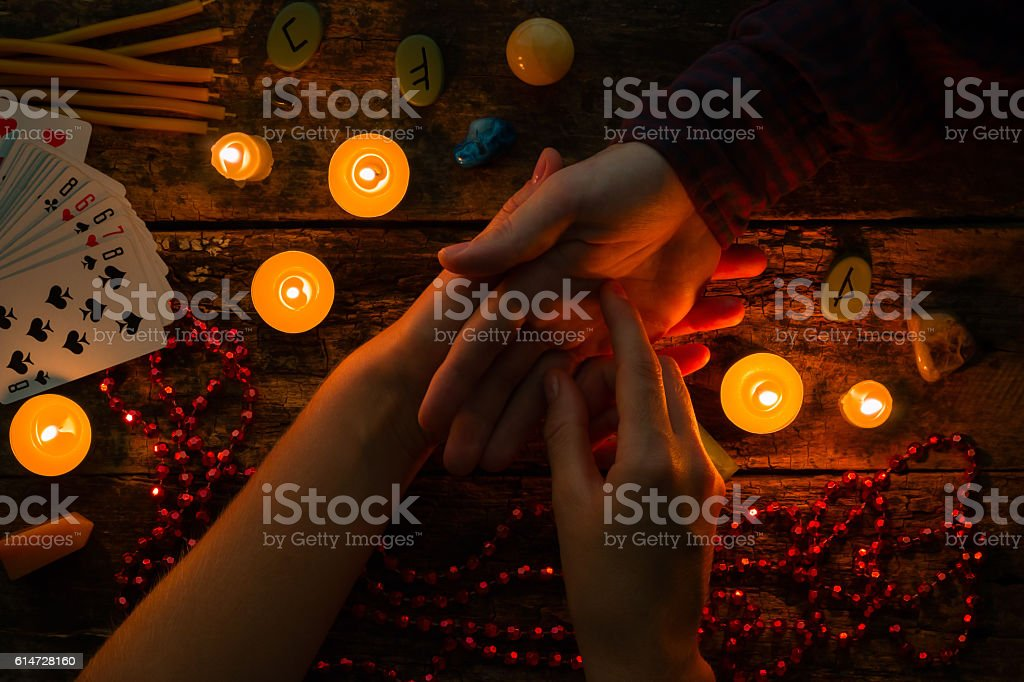 fortuneteller reads fortunes by hand with candles and runes – Foto
