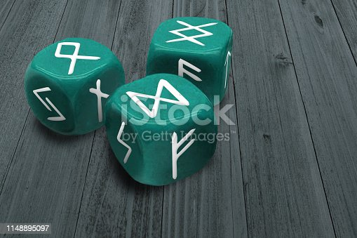 Fortunetelling or Horoscope charting concept. Three dices with Runes signs symbols on faces. Prediction or astrology medium esoteric stuff. Macro of green gambling cubes on wooden table background
