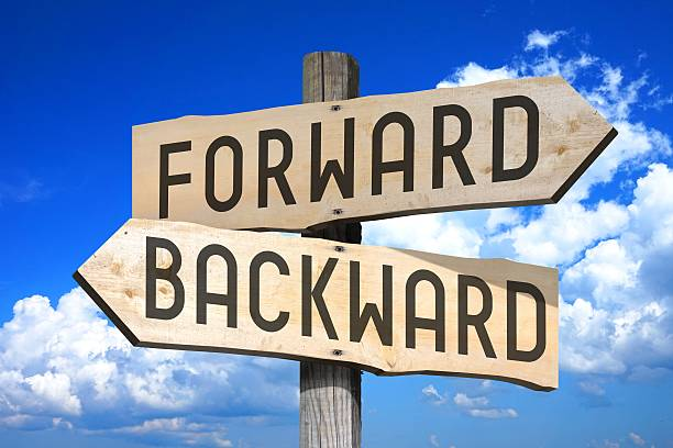 "Forward, backward - wooden signpost Wooden signpost with two arrows - ""Forward"", ""Backward"", sky with clouds in a background.  bending over backwards stock pictures, royalty-free photos & images"