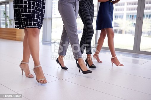 Cropped shot of a group of young businesswomen walking through a modern office