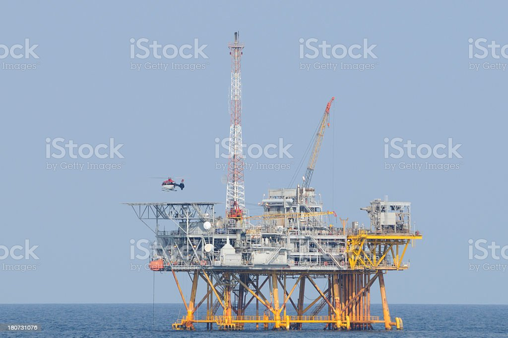 Fossil fuel production platform with helicopter royalty-free stock photo