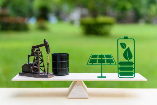 fossile brennstoffe vs erneuerbare / zukunft saubere alternative energiekonzept: petroleum bohrschwengels, trommel-fass rohöl und solar-panel, grüne batterie mit blatt auf ein einfaches holz balance skala in gleicher lage - opec stock-fotos und bilder