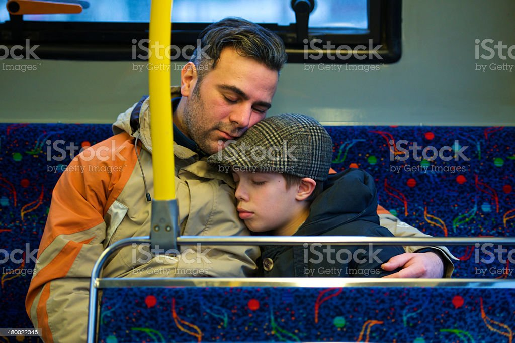 Foster care father and son embrace  sleeping in bus stock photo