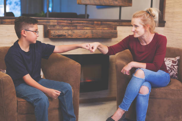 Foster Care Woman and Boy Child Talking Foster Care Woman and Boy Child Talking inside a retro home Anglo American stock pictures, royalty-free photos & images