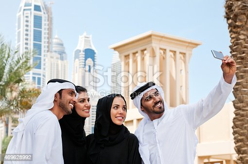 491496340 istock photo Fouir friends in traditional Emirati clothes doing a selfie in Dubai. 469628992