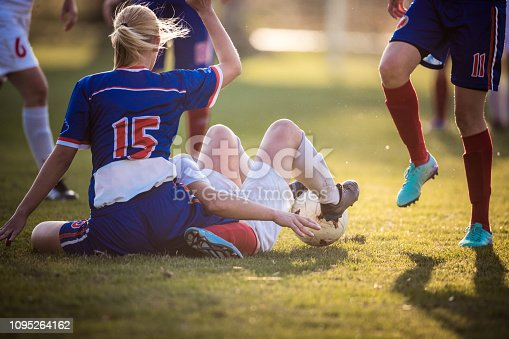 Female soccer players on the ground after the foul during a match on playing field.