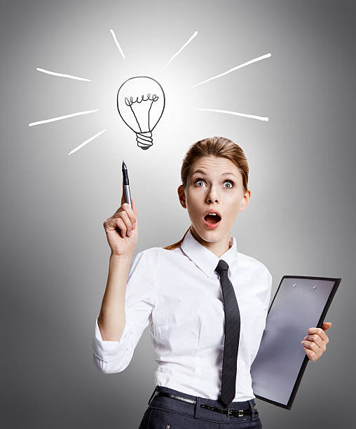 Found a way out attractive woman wearing a white shirt with a tie and a folder in her hand enthusiastic about the idea - on grey background deem stock pictures, royalty-free photos & images