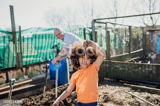 Little boy is holding an earthworm up to the camera which he has found while working with his grandfather on the farm.