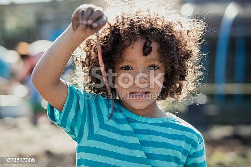 Little boy is proudly showing the camera an earthworm that he has found.