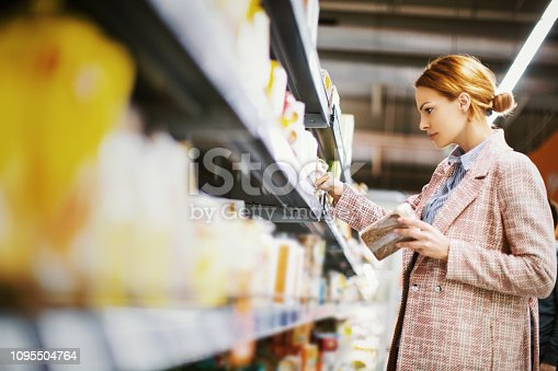Young woman buying gluten free bread at supermarket.