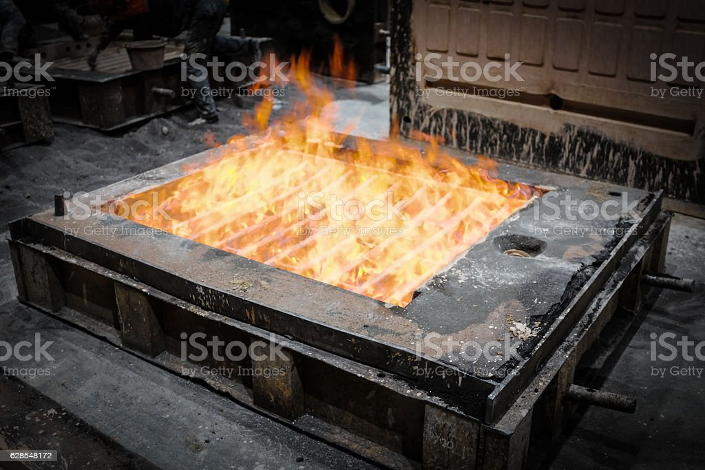 Foundry worker melting metal for casting spare parts - Photo