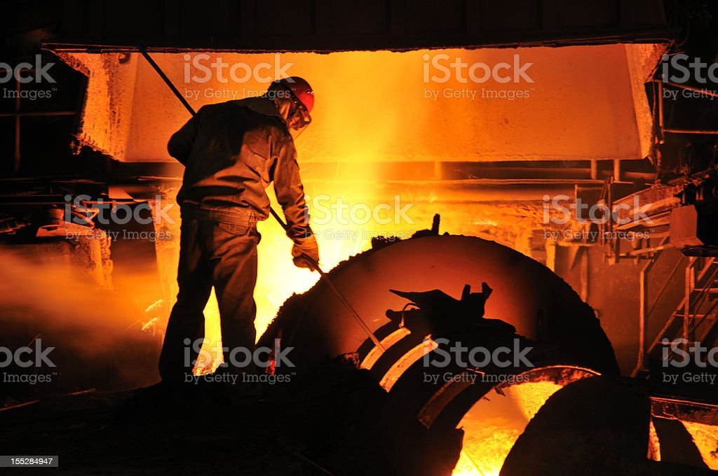 Foundry worker shoveling molten metal in a furnace stock photo