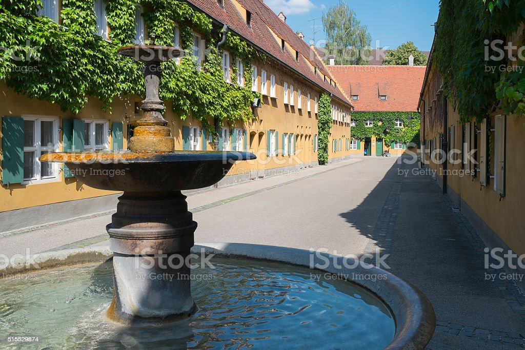 Fountain and apartments in the Fuggerei in Augsburg stock photo