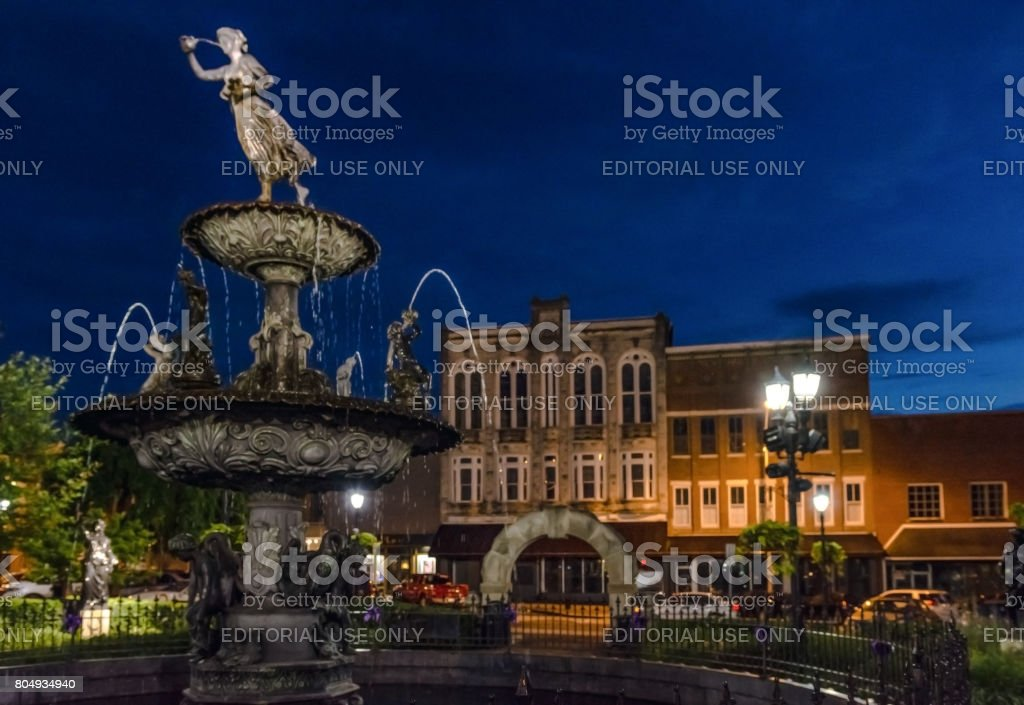 Fountain in Bowling Green's town square during blue hour stock photo