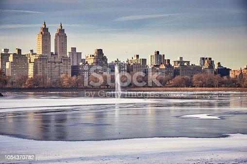 fountain in Jacqueline Kennedy Onassis Reservoir in winter season, skyline of west side Manhattan