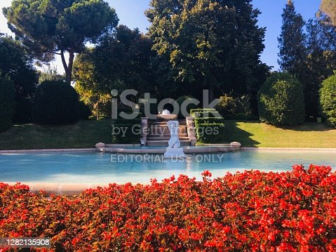 21 August, 2018 - Barcelona, Spain: Fountain in Jardins del Palau de Pedralbes park surrounded by bright red flowers. Majestic, romantic and luxuriant garden in Barcelona, in French and English style.