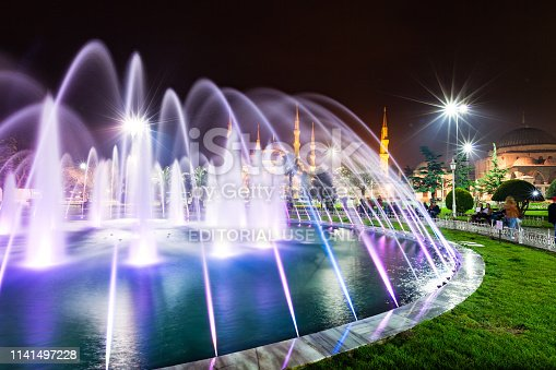 People sit besides an illuminated fountain in Sultanahmet Park, with the Blue Mosque in the background.