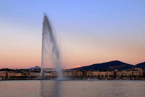 Fountain of Geneva and snowcapped mountains at twilight