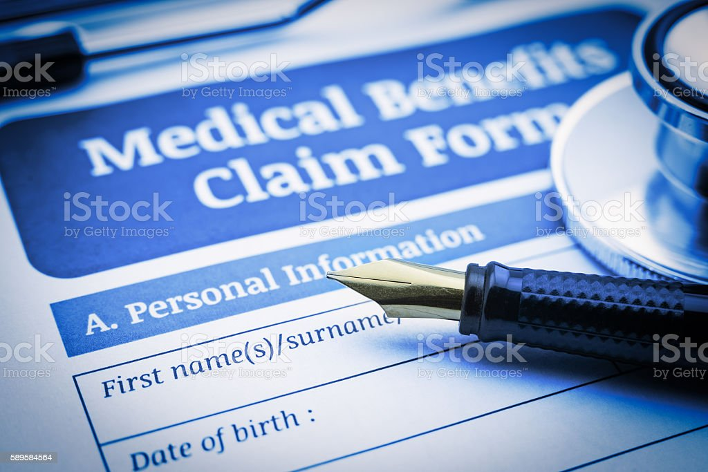 Fountain pen, a stethoscope and a medical benefit claim form. stock photo