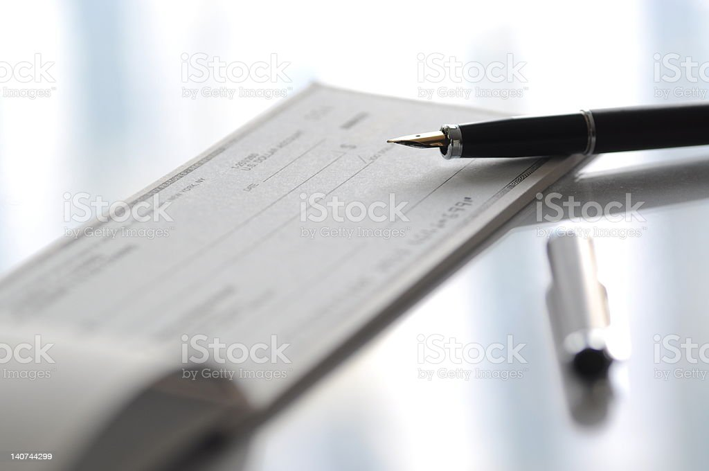 Fountain pen and check on table stock photo