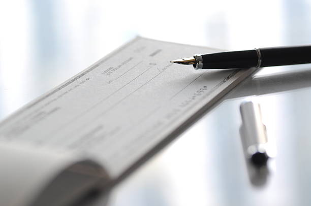 fountain pen and check on table - blank check stock photos and pictures