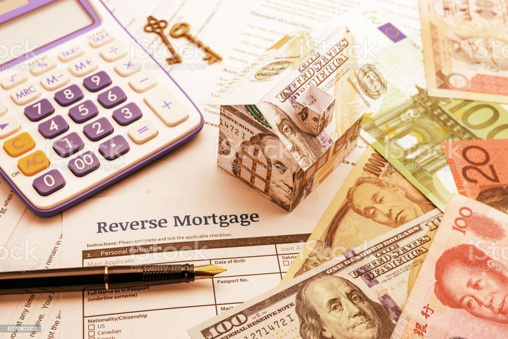 Fountain pen, brass keys, a calculator, a dollar paper house and a blank reverse mortgage form with banknotes. stock photo