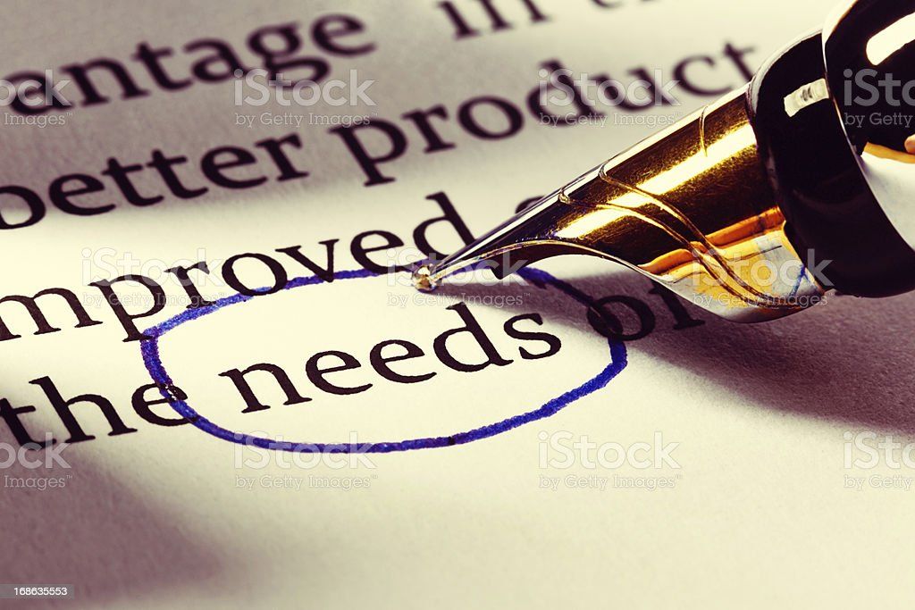 """Fountain pen circles the word """"needs"""" in business document royalty-free stock photo"""