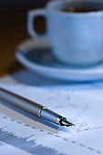 Fountain pen, cup of coffee and stock chart in blue lighting. Shallow DOF
