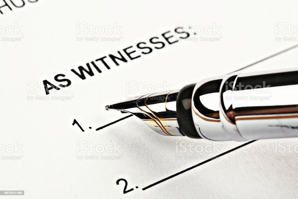Fountain pen hovering above 'Witness' section of official document stock photo