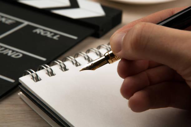 füllfederhalter in den händen eines drehbuchautors auf dem hintergrund eines filmklatschers und eines notizbuchs - drehbuchautor stock-fotos und bilder