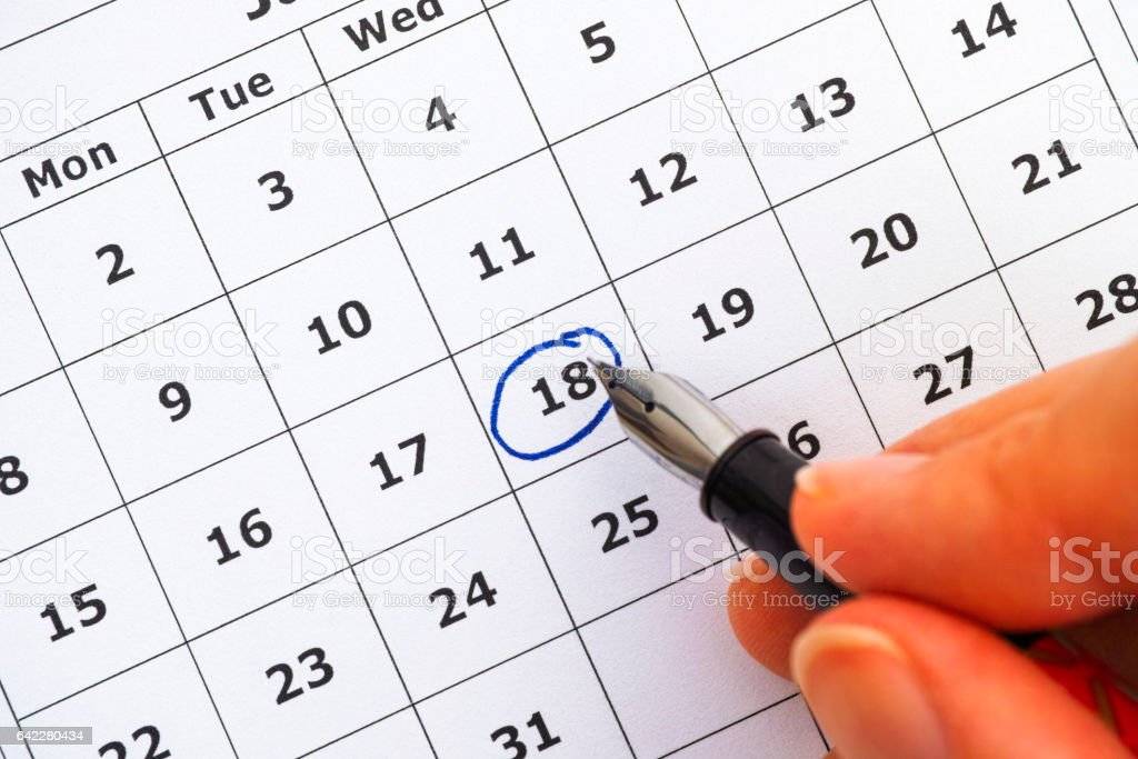 Fountain pen in woman hand marking day on calendar. stock photo