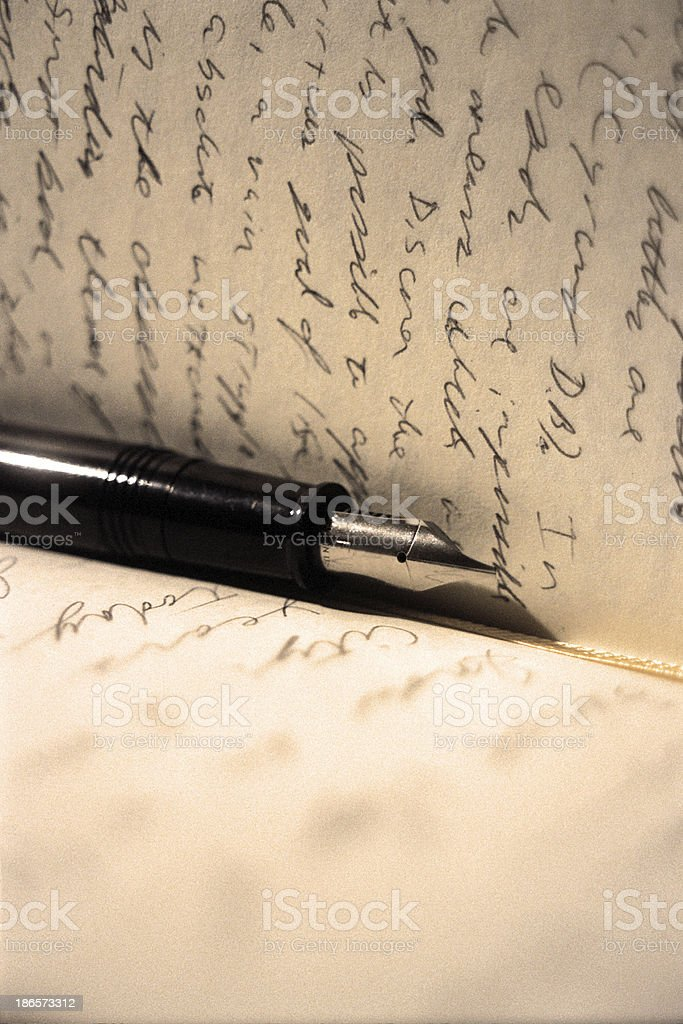 A black and silver fountain pen rests between the pages of a man\'s...