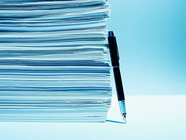 Fountain pen leaning against stack of paper  bureaucracy stock pictures, royalty-free photos & images