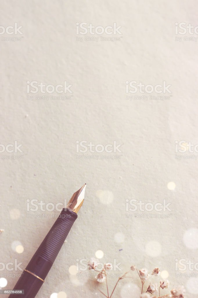 Fountain pen on aged blank paper; copy space stock photo