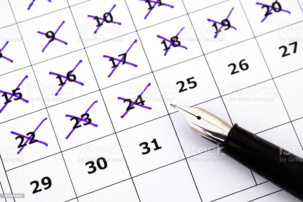 Fountain pen on calendar with marking days stock photo
