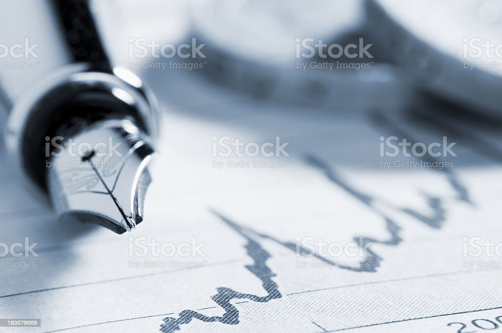 Fountain pen on graph in newspaper with coins stock photo