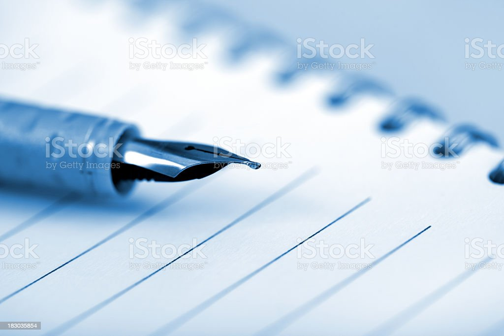 Close-up of a fountain pen lying on a spiral bound notebook in blue...