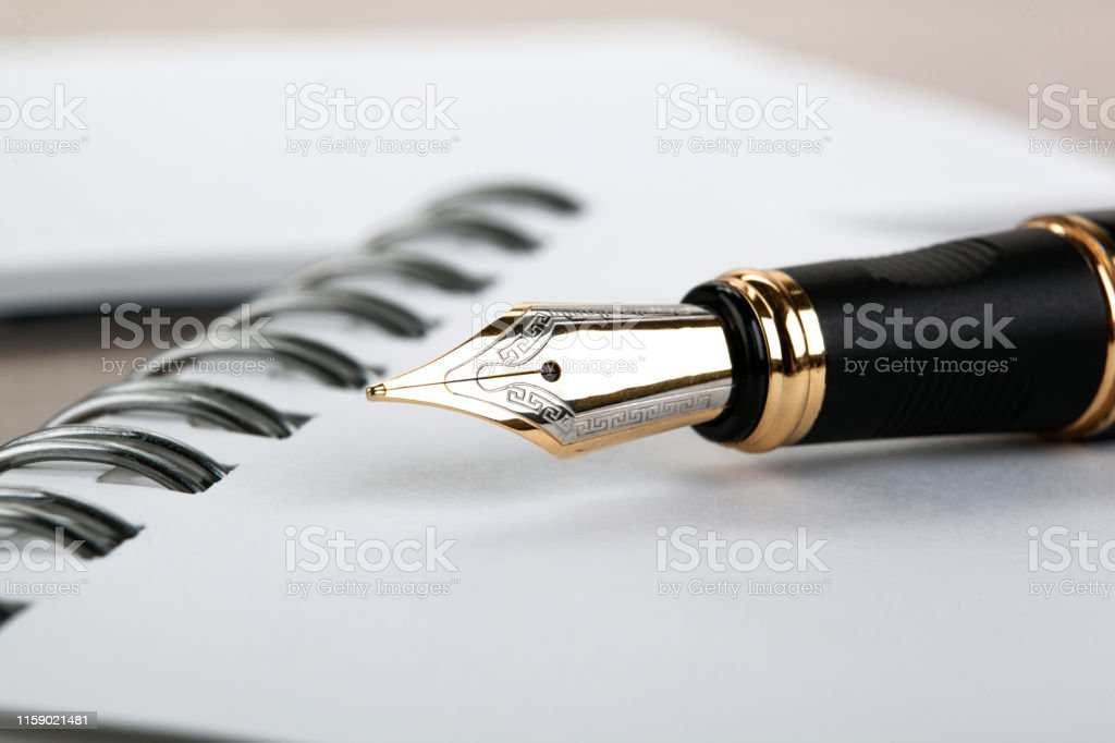 fountain pen on the notepad on a table closeup